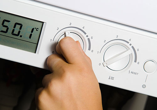 Photo of an engineer adjusting a thermostat